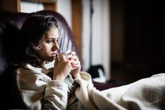 Mujer enferma en la cama, llamando en enfermo, día libre del trabajo Infusión de hierbas de consumición Vitaminas y té caliente p Fotografía de archivo libre de regalías
