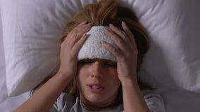 Mujer enferma en la cama que pone la toalla en la frente, sufriendo de gripe, tratamiento almacen de video