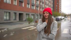 Mujer enferma femenina joven, muchacha con dolor de la garganta dolorida y tos desagradable, tosiendo en la calle afuera, atenció almacen de video