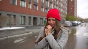 Mujer enferma femenina joven, nariz que sopla de la muchacha a la servilleta de papel y estornudo en el exterior de la calle, ate almacen de metraje de vídeo
