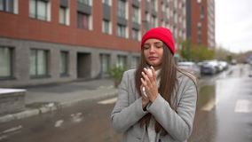 Mujer enferma femenina joven, nariz que sopla de la muchacha a la servilleta de papel y estornudo en el exterior de la calle, ate almacen de video