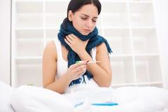 Mujer enferma gripe Muchacha con la mentira fría debajo de una manta que sostiene a Imagen de archivo libre de regalías