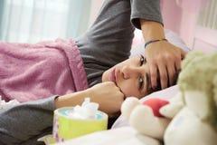 Mujer enferma hispánica en cama con dolor de cabeza y gripe Fotos de archivo