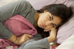 Mujer enferma hispánica en cama con los calambres y el dolor menstrual que miran la cámara Fotos de archivo libres de regalías