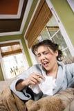 Mujer enferma joven que estornuda imagenes de archivo