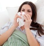 Mujer enferma joven que miente en el sofá Foto de archivo