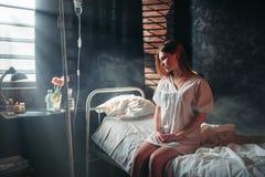 Mujer enferma joven que se sienta en cama de hospital en goteo foto de archivo
