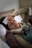 Mujer enferma joven que tiene gripe de la alta fiebre foto de archivo libre de regalías