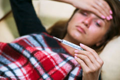 Mujer enferma que miente en el sofá debajo de la manta de las lanas y que mira el termómetro foto de archivo