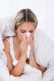 Mujer enferma que sopla su nariz Imagen de archivo