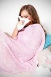Mujer enferma que sopla su nariz Imagenes de archivo