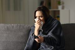 Mujer enferma que sopla y que ve la TV en casa Foto de archivo libre de regalías