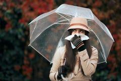 Mujer enferma que sostiene el paraguas en Autumn Rain Blowing Her Nose imagenes de archivo