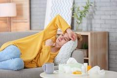 Mujer enferma que sufre de frío en el sofá imágenes de archivo libres de regalías