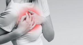 Mujer enferma que tiene mún ataque del corazón al dolor y al dolor imagenes de archivo