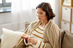Mujer enferma que toma la medicina con agua en casa fotos de archivo