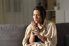 Mujer enferma que toma la píldora solamente en la noche en casa Fotografía de archivo