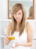 Mujer enferma que toma píldoras en el cuarto de baño Fotos de archivo