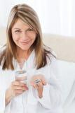 Mujer enferma que toma sus píldoras Foto de archivo
