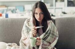 Mujer enferma que toma temperatura Imagenes de archivo