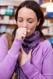 Mujer enferma que tose en farmacia Fotografía de archivo