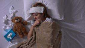 Mujer enferma sola que abraza el oso del juguete que miente en cama con la compresa y los tejidos metrajes