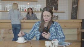 Mujer enfocada del freelancer que trabaja en el teléfono en café almacen de video