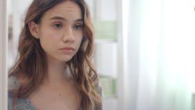 Mujer enfocada que pone en las lentes de contacto en espejo delantero del cuarto de baño del ojo almacen de video