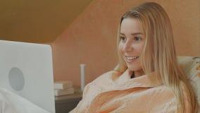 Mujer enfocada que usa el ordenador portátil que tiene charla video mientras que miente en cama de hospital imagen de archivo libre de regalías