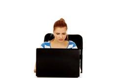 Mujer enojada adolescente con el ordenador portátil que se sienta detrás del escritorio Fotos de archivo libres de regalías