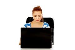 Mujer enojada adolescente con el ordenador portátil que se sienta detrás del escritorio Imágenes de archivo libres de regalías