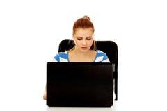 Mujer enojada adolescente con el ordenador portátil que se sienta detrás del escritorio Fotografía de archivo libre de regalías