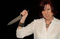 Mujer enojada con el cuchillo imagenes de archivo
