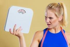 Mujer enojada con la escala, tiempo de la pérdida de peso para adelgazar imagenes de archivo