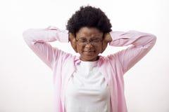 Mujer enojada de la raza mixta que tapa sus oídos imágenes de archivo libres de regalías