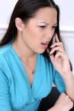 Mujer enojada en el teléfono celular Imagenes de archivo