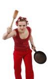 Mujer enojada en los rodillos del pelo, sosteniendo un sartén. Fotografía de archivo
