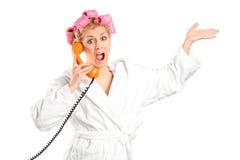 Mujer enojada en una albornoz que grita en un teléfono Imagen de archivo libre de regalías