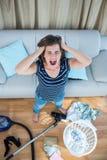 Mujer enojada en una sala de estar caótica con el aspirador Imagen de archivo libre de regalías