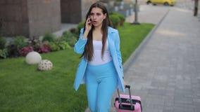 Mujer enojada, enfadada que habla por el tel?fono en ciudad y smartphone que lanza almacen de video
