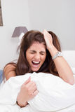 Mujer enojada joven en la cama que tira de su pelo y que grita Foto de archivo