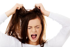 Mujer enojada joven que tira de su pelo Fotos de archivo libres de regalías