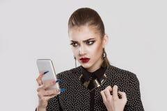 Mujer enojada, mirando curiosamente en el teléfono, ella no le gusta lo que ella ve imagenes de archivo