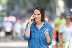 Mujer enojada que demanda en el teléfono en la calle Fotos de archivo libres de regalías
