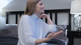 Mujer enojada que grita mientras que se sienta en cama en dormitorio metrajes