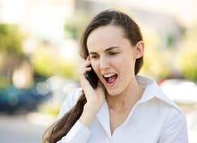Mujer enojada que habla en un teléfono Foto de archivo libre de regalías