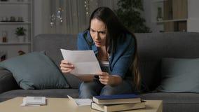 Mujer enojada que lee una letra en la noche almacen de video