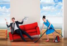 Mujer enojada que limpia con la aspiradora mientras que el hombre está descansando Foto de archivo libre de regalías
