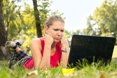 Mujer enojada que mira en computadora portátil Foto de archivo libre de regalías
