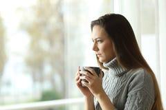 Mujer enojada que mira a través de una ventana Imágenes de archivo libres de regalías